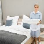 Housekeeper Holding Stack Of Sheet